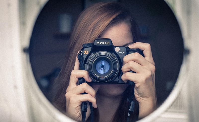 Woman looking through a camera, taking photo into a mirror