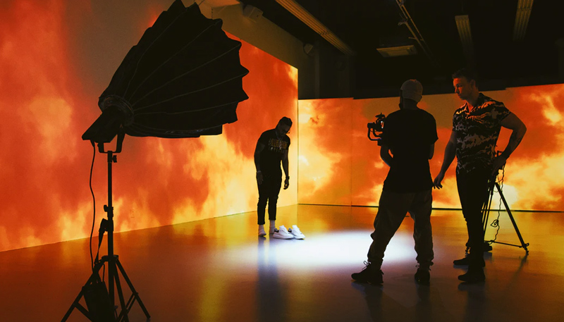 Videographers discuss a shot behind the scenes of a shoot in a warehouse. The subject stands waiting against a backdrop of orange clouds projected on the walls. A camera flash in a directional housing is set up in the left foreground.