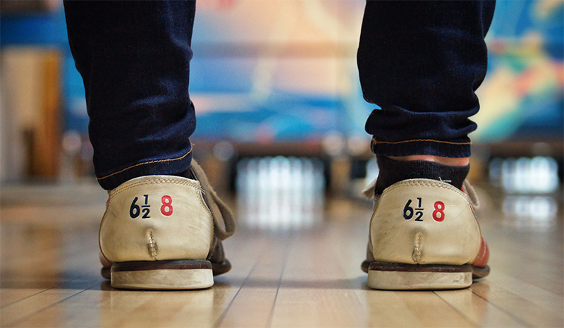 View of 10 bowling pins between the legs of a bowler