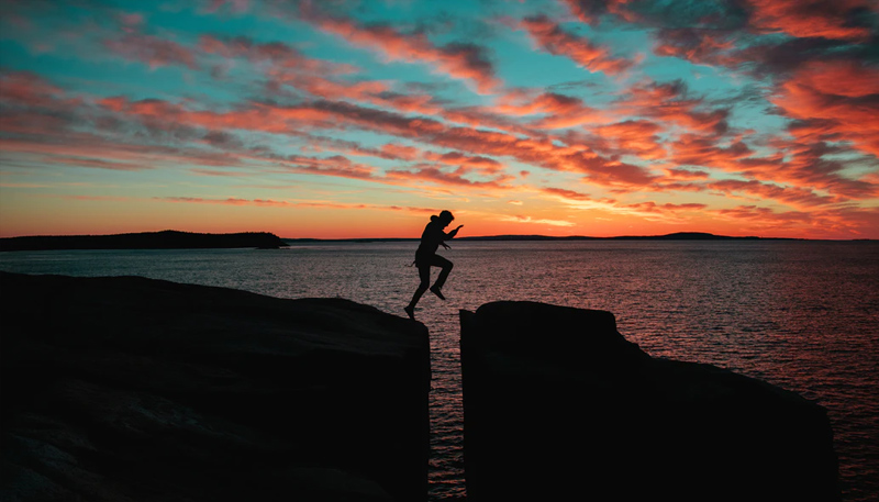 Silhouette of a person leaping over a gap between two rocks. Behind that, the ocean stretches to an orange sunset.