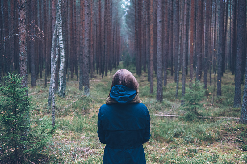 Woman looking into woods