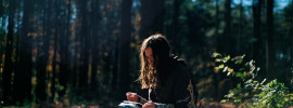A woman reading in the woods