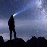 Man shining headlamp toward the night sky