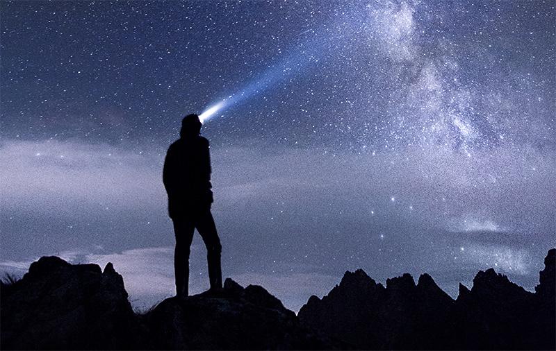 Person shining headlamp toward the night sky