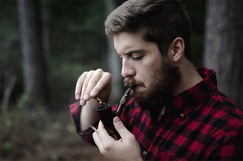 Guy lighting a pipe