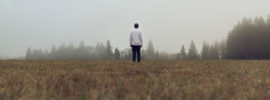 Person standing alone in a foggy field.
