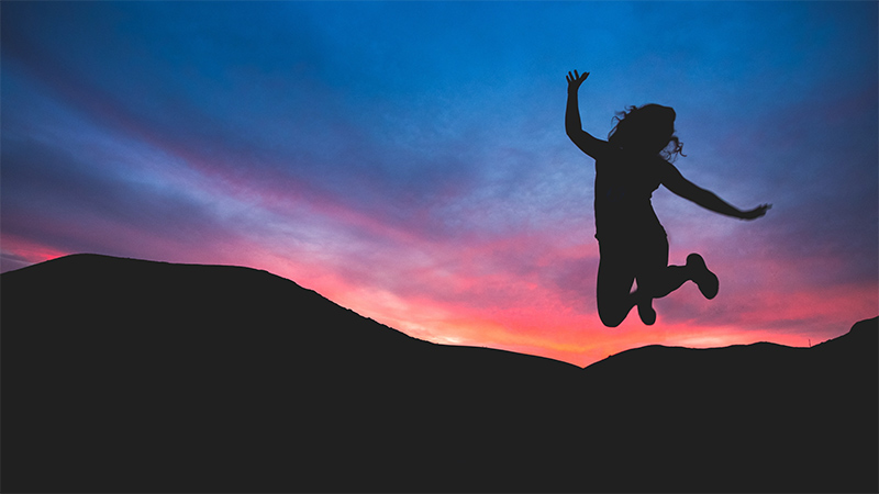 A woman jumping in front of a sunset.