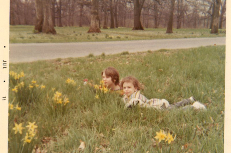 My sister and my pancho-ed self in the grass (1971)