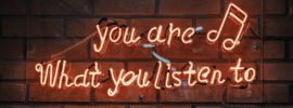 "Neon sign reading ""You are what you listen to."""