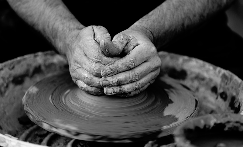 Hands shaping a bowl on a potter's wheel