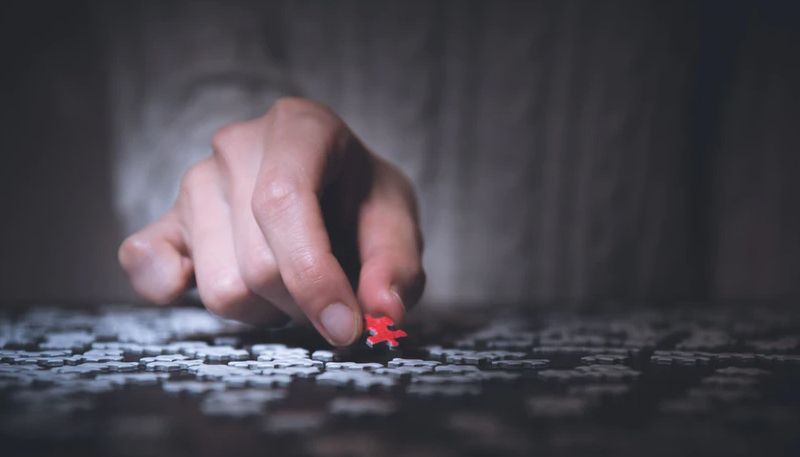 A hand places a red puzzle piece into a jumbled spread of white puzzle pieces.