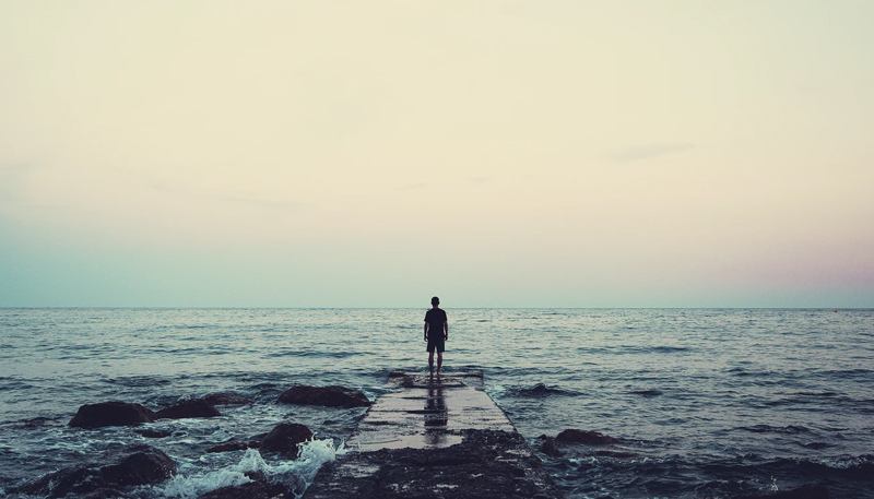 A person stands at the end of a concrete pier while staring at a roiling ocean.