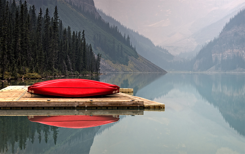 Red canoes on a pier on a still lake.