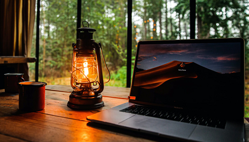 A wood-plank desk with (Left to Right) two metal camping mugs, a lit lantern, and a laptop computer.  Behind them, though a window, green trees at dusk...