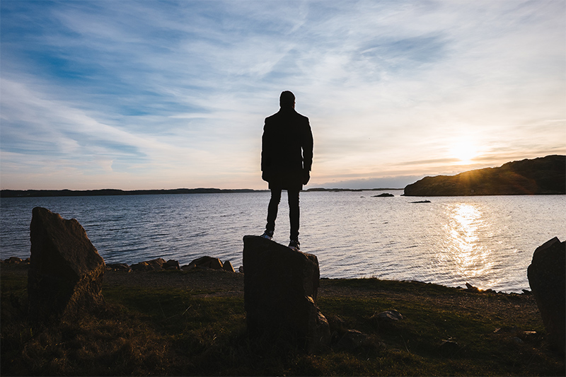 Person standing on a rock at sunset