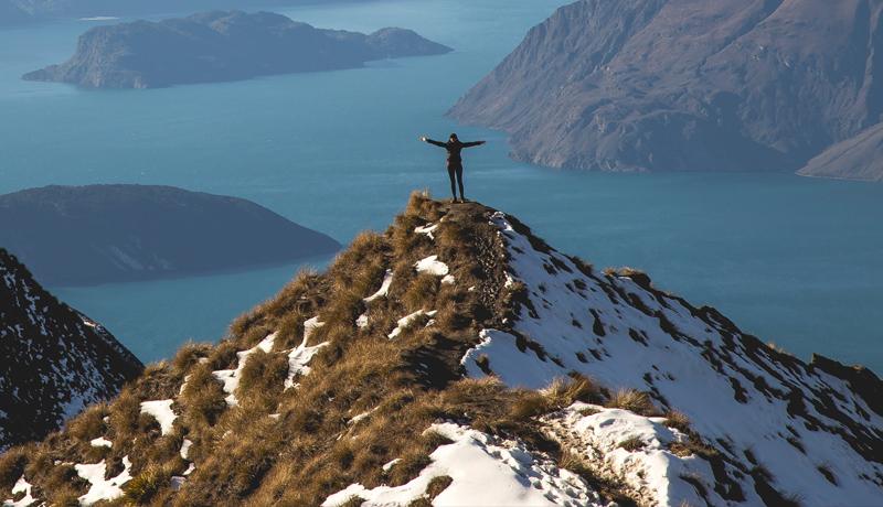 Woman standing on mountain summit