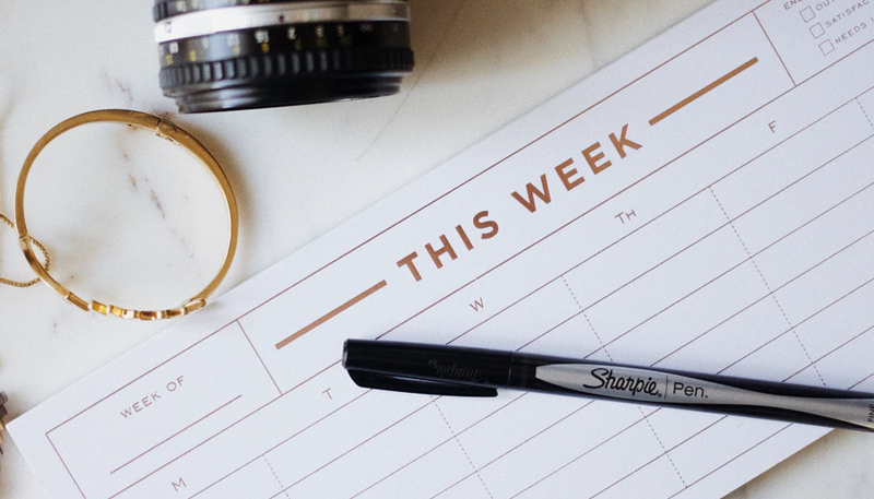 A Sharpie brand pen rests on top of a weekly calendar reading THIS WEEK across the top. Also in the photo, a bit of a camera lens.