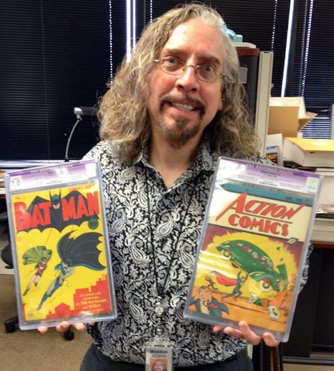 Weldon Adams holding Batman #1 and Action Comics #1.